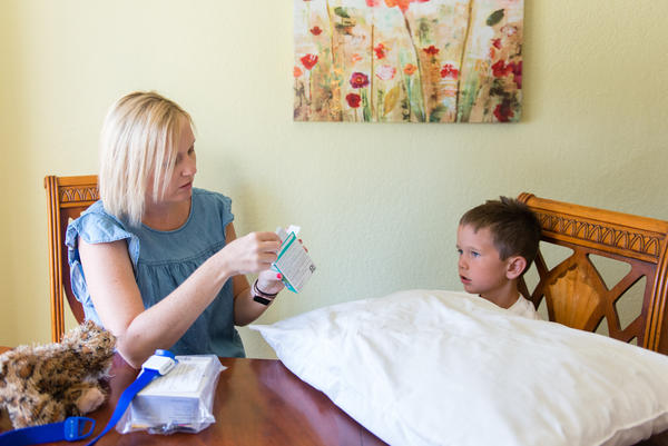 Jessica Morris prepares to inject a blood-clotting protein into son Landon's arm at their home in Yuba City, Calif.