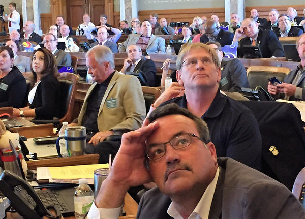 Members of the Kansas House look at the voting board after debate of a school funding bill Monday. The House and Senate approved a plan to add about $300 million over two years for Kansas schools.
