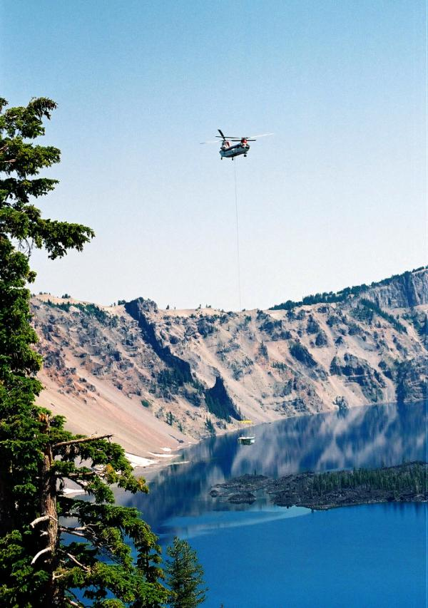A helicopter ferries a tour boat into Crater Lake at Crater Lake National Park in Oregon. Park management will be evaluating how the noise affects the soundscape and park wildlife.