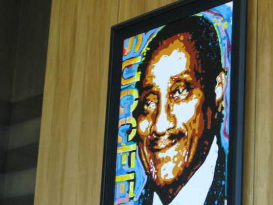 """A portrait of Johnson Publishing Co. founder John H. Johnson hangs in the company's lobby, embellished with the word """"succeed."""" <em>Ebony's </em>September issue included an article on how to raise a high achiever."""