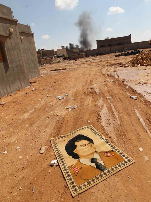 <p>A small carpet with the portrait of Gadhafi lies on the ground near fighting at the front line of Bani Walid, southeast of Tripoli, earlier this month.</p>