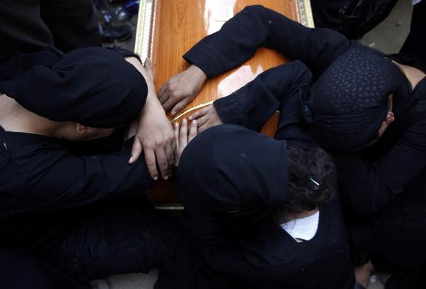 <p>Women mourn over the coffin of a Coptic Christian killed during the clashes</p>