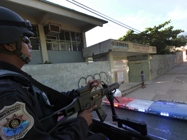 <p>A federal policeman in Mexico patrols the outskirts of Acapulco, Guerrero state, earlier this month. Acapulco has seen a sharp drop in tourism as criminals battle for control of the city. </p>