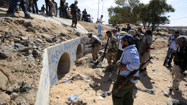 <p>Libyan Transitional National Council fighters said Moammar Gadhafi was captured Thursday in this graffitti-filled culvert in Sirte.</p>
