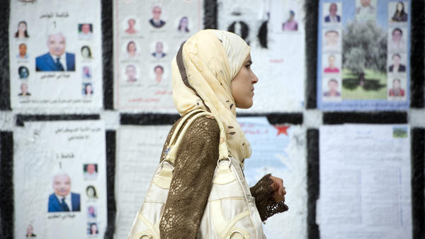 <p>A Tunisian woman in the capital, Tunis, walks past a wall covered with posters of political candidates, on Oct. 20. Tunisia touched off the Arab uprisings this year, and it is holding elections Sunday to draw up a new constitution.</p>