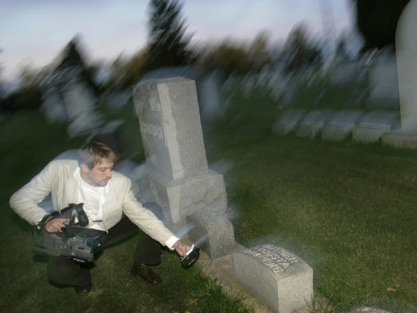 <p>Paranormal investigator Noah Voss points a video camera at an electromagnetic frequency device to record any abnormal activity at the Sun Prairie Cemetery in Sun Prairie, Wis.</p>
