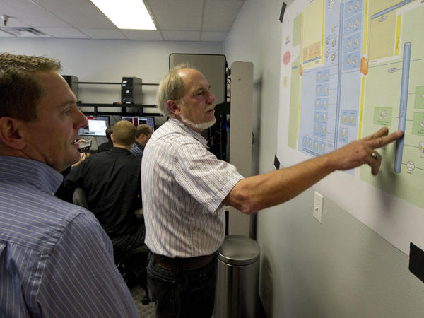 Cybersecurity analysts look at a diagram that shows their computer network, which is coming under attack, during a mock exercise at the Idaho National Laboratory in September.