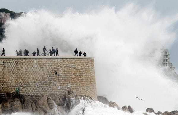 A U.N. climate panel says that we can expect more extreme weather conditions as a result of climate change. Above, people run from a high wave on Nov. 8 in Nice, France, where heavy rain and flooding forced hundreds to evacuate.