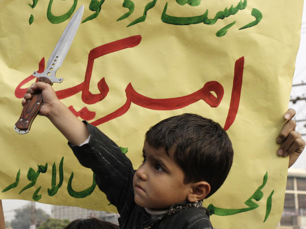 """A Pakistani boy holds a dagger before a placard reading """"Who is terrorist, America"""" during a rally Sunday in Lahore, Pakistan, to condemn NATO helicopter attacks on Pakistani troops. Despite new tensions that have arisen from the raid, some observers say the U.S. and Pakistan have little choice but to continue to work together."""