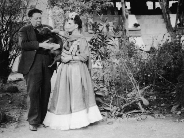 Diego Rivera holds a pet dog alongside his wife, artist Frida Kahlo, in Mexico City, Mexico.