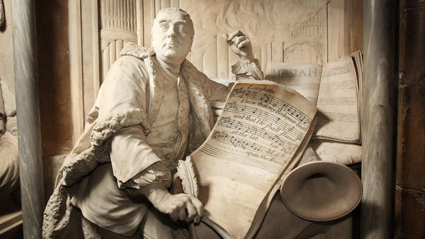 A statue of George Frideric Handel, posing with his <em>Messiah</em> transcript, at London's Westminster Abbey.