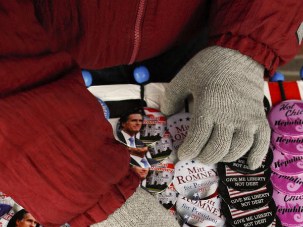 A volunteer arranges buttons before Mitt Romney speaks Wednesday in Clinton, Iowa.
