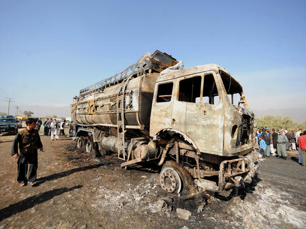 Afghan policemen and locals watch a burned-out fuel truck, supplying a U.S.-run base, after being targeted by a bomb near Bagram Air Field near Kabul on Oct. 26. Attacks on convoys carrying supplies to U.S. troops are costly — both in monetary terms and in human life.