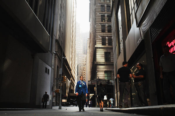 A trader walks in New York City's financial district on Sept. 12, a day when stocks fell early based on fears that the Greek government would default, then rallied on news that China might buy Italian debt. This year, what sent the market into a tailspin often took place overseas.