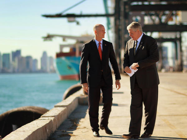 """Port of Miami Director Bill Johnson (right) speaks to Florida Gov. Rick Scott at the port. """"It is the game changer,"""" Johnson says of the city's plan to deepen its port to accept new, larger ships from the Panama Canal."""