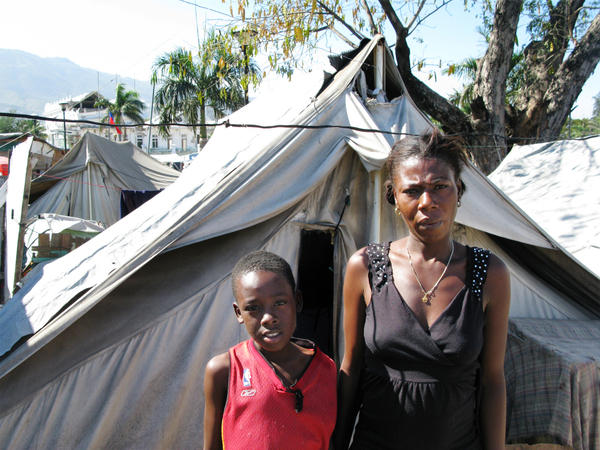 """Gerline Rousole, 22, stands next to her son, Savoiu, 7, in Place Pigeon, a displaced-person camp outside the National Palace in Port-Au-Price. Both of Rousole's parents died in the Jan. 12, 2010, earthquake. """"If my parents were still alive, I wouldn't be here,"""" she says."""