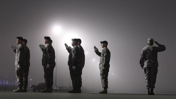An Army carry team salutes a vehicle containing the remains of an American soldier killed in Afghanistan on March 17, at Dover Air Force Base in Dover, Del.