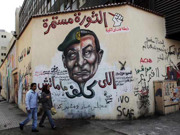 """A mural in Cairo depicts the split faces of Egyptian military ruler Field Marshal Hussein Tantawi, left, and ousted president Hosni Mubarak accompanied by Arabic that reads, """"who assigned you did not die, No for gas export to Israel, the revolution continues."""""""