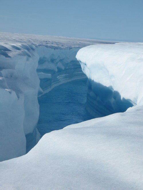 Rushing water at the end of a lake has cut a deep channel into the ice. Greenland's ice contains enough water to raise sea levels by 20 feet.