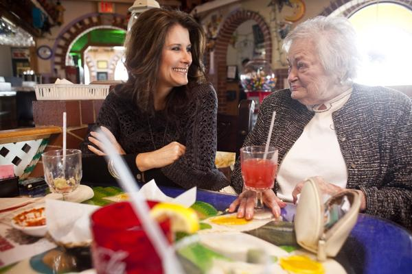 Kelley Hawkins (left) smiles with her grandmother AnnaBelle Bowers, 87, while at lunch in Harrisburg, Pa. Kelley shares full-time care of AnnaBelle with her sister-in-law LaDonna Martin. Both are nurses with two children each, and move Annabelle, who has limited mobility, every two weeks from one home to another.