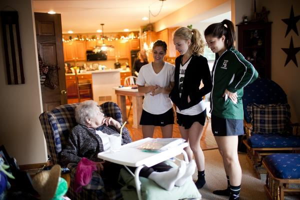 """AnnaBelle talks to her granddaughter Carley (right) and Carley's friends after they returned from lacrosse practice. """"I'm not rich money-wise, but with my family I'm a millionaire,"""" AnnaBelle says."""