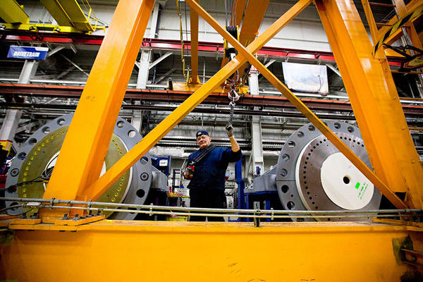 Angel Gonzales operates a crane to assemble a gear box for a wind turbine. The heavy-lift cranes hoist pieces weighing up to 70 tons.