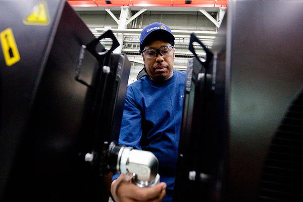 """About 175 people work at Gamesa's factory, including Jerry """"Jazz"""" Holt, who is assembling an oil cooler unit."""