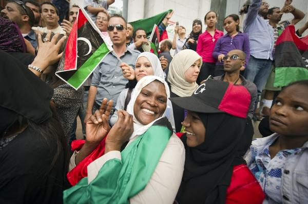 Tunisians and Libyans living in Tunisia wave Libya's National Transitional Council flags in celebration.