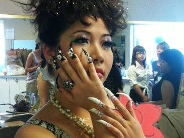 A model shows off an ABC student's work. Most of the students are studying manicuring.