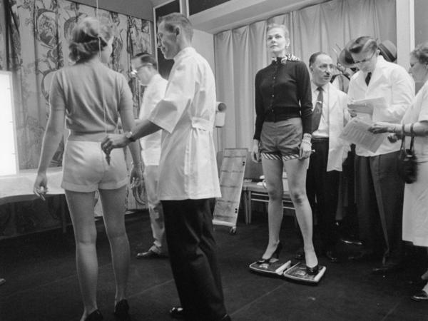 How straight is her spine? A chiropractor uses a plumb bob to find out. Across the room another contestant straddles two scales so chiropractors can evaluate her posture.