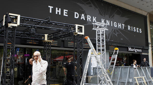 Workers dismantle an installation that was set up for the premiere of <em>The Dark Knight Rises</em> in Paris. It had been scheduled for Friday night but was canceled after a gunman killed 12 people at a Colorado opening of the same film.