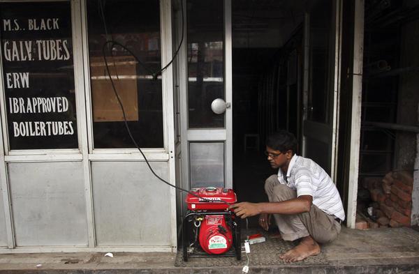 A shopkeeper fixes an electric generator at his shop in New Delhi.