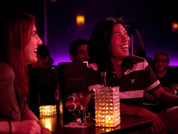 Megan Lutz, left, and Justin Chun react to amateur comedian Robert Lynch at the Metropolitan Room in Manhattan, N.Y. Lynch is an anthropologist researching what laughing reveals about us.