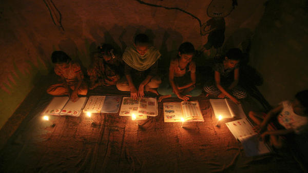 Muslim girls study by candlelight inside a religious school in Noida, near New Delhi, on July 31. The collapse of three regional power grids last week caused a massive power outage that blacked out more than half of India.