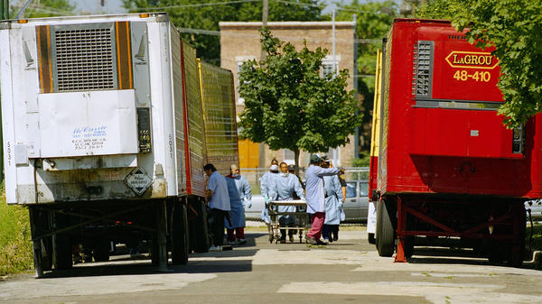 Cook County morgue workers walk between a row of refrigerated trucks outside the morgue in July 1995, when a deadly heat wave struck Chicago.