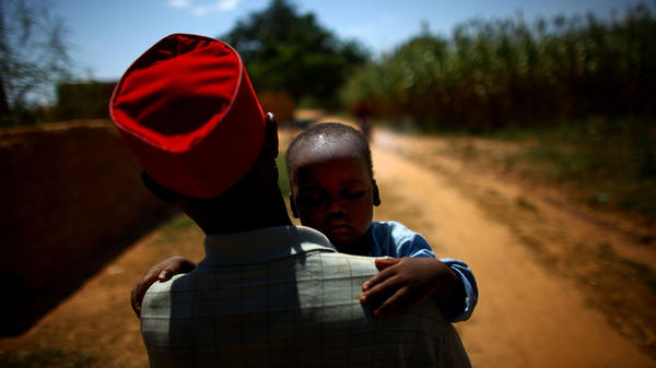 Ado Ibrahim carries his son Aminu through a village in northern Nigeria. Aminu was paralyzed by polio in August.