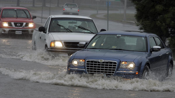 Motorists drive through standing water at an intersection flooded from the remnants of Tropical Storm Ida in the Ocean View area of Norfolk, Va., in November 2009.