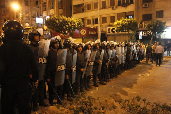 Egyptian riot police stand guard in Cairo on Wednesday during large-scale clashes that marked the worst violence of a deepening crisis over the disputed constitution.