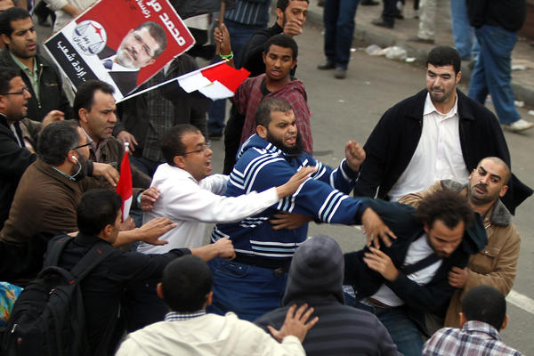 Supporters of the Muslim Brotherhood attack an opposition protester in front of the presidential palace.