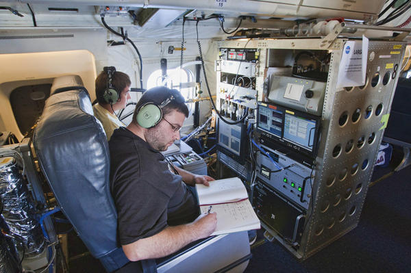 Terry Lathem, a graduate student in Georgia Tech's School of Earth and Atmospheric Sciences, takes notes aboard a NASA DC-8 aircraft gathering samples of microorganisms in the atmosphere.