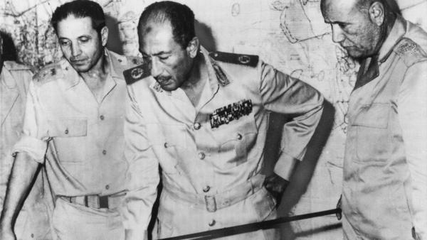 Egyptian President Anwar Sadat is flanked by senior military officers as he reviews maps of battlefield developments in the 1973 Arab-Israeli War. He's shown at army headquarters in Cairo on Oct. 15, 1973. Egypt and Syria attacked Israel, catching Israel and the CIA off-guard.