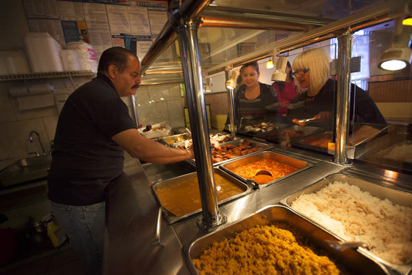 Miguel Fontanez Sr., the owner and founder of Pioco's Chicken in Kissimmee, Fla., serves customers at his restaurant. He opened the restaurant 11 years ago, and it has become a hub for the area's large Puerto Rican community.