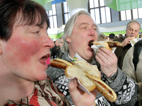 """Visitors eat rostbratwurst sausages at the """"Green Week"""" agriculture fair in Berlin in January 2011."""