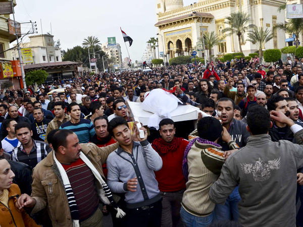 Egyptians carry the body of a person killed in clashes between police and protesters in Mansura on Saturday. Mansura is the latest province to launch a campaign of civil disobedience, following in the footsteps of the canal cities of Port Said, Ismailiya and Suez.