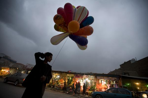 An Afghan boy selling balloons waits for customers in Kabul, 2009.