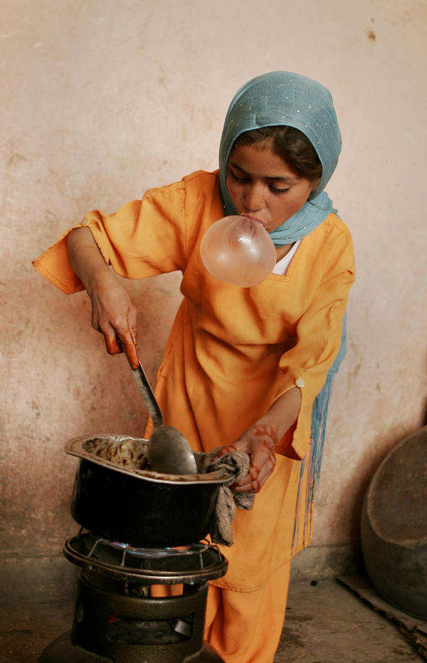An Afghan girl blows bubble gum while cooking for her family in Kabul, 2007.