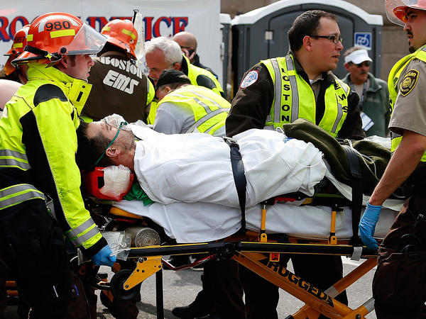 An injured man is loaded into an ambulance after two explosions during the 117th Boston Marathon near Copley Square on Monday.