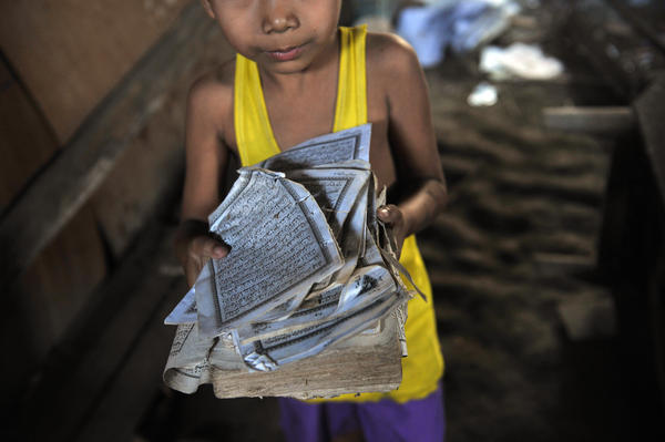 A boy shows the torn pages of a Quran at his home after sectarian violence spread through Zeegone, about 90 miles north of Yangon, in late March. More than 100 people were killed in similar incidents in the country's west last year.