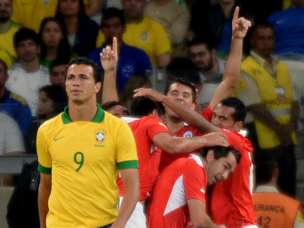 Chile's Marcos Gonzalez (center) celebrates with teammates after scoring against Brazil during their friendly football match on April 24.