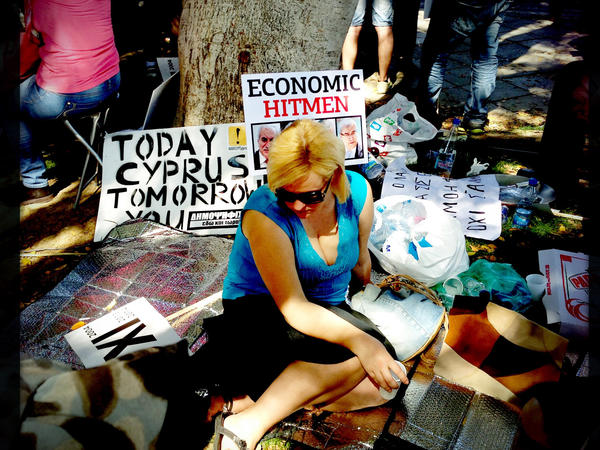 A Cypriot left-wing supporter sits in the shade during a protest outside the Parliament in Nicosia on Tuesday.